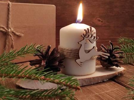 Kompozycja świąteczna ze świecą i jeleniem.